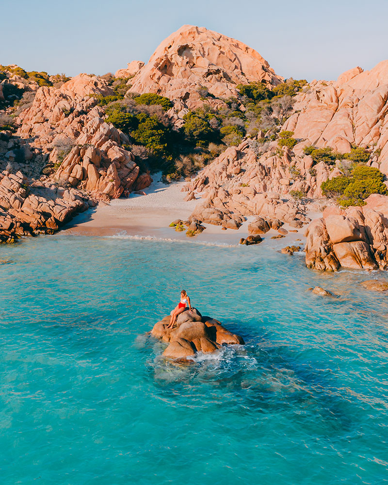 Drone shot of me in Sardinia, Cala Coticcio beach with blue sea and a rocky beach