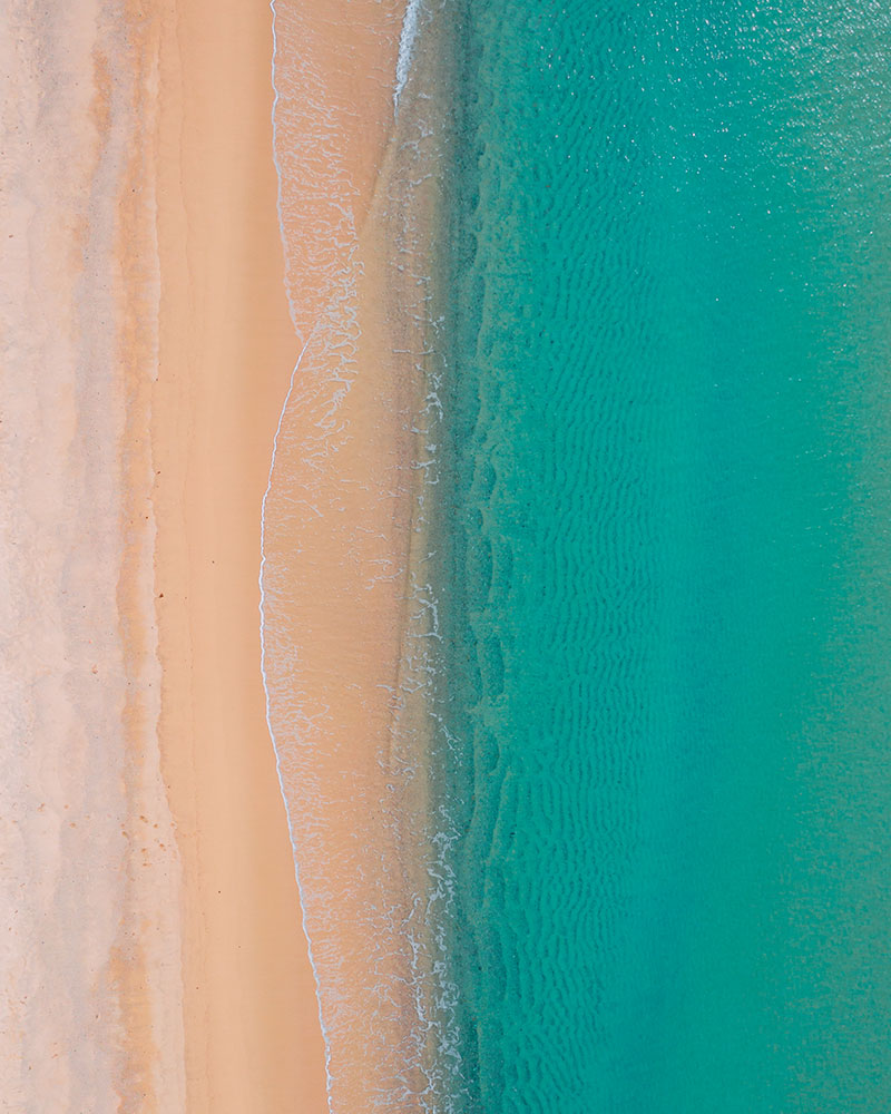 Drone shot of the beach in Sardinia with sea and sand