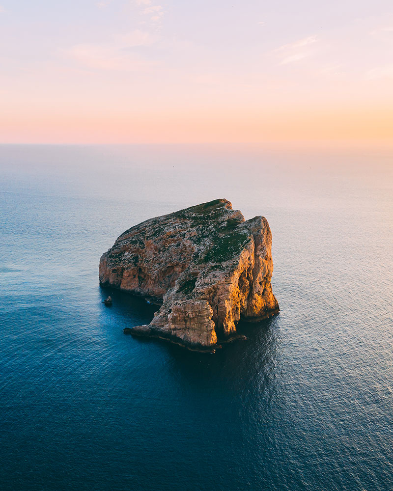 Capo Caccia in Sardinia - a rock in the sea in Northern Sardinia at sunset