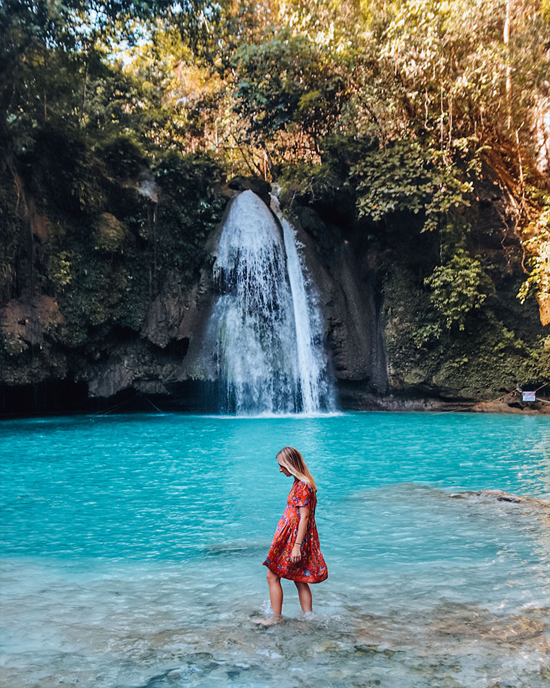 Girl in front of Kawasan falls in Cebu, Philippines with clear blue water