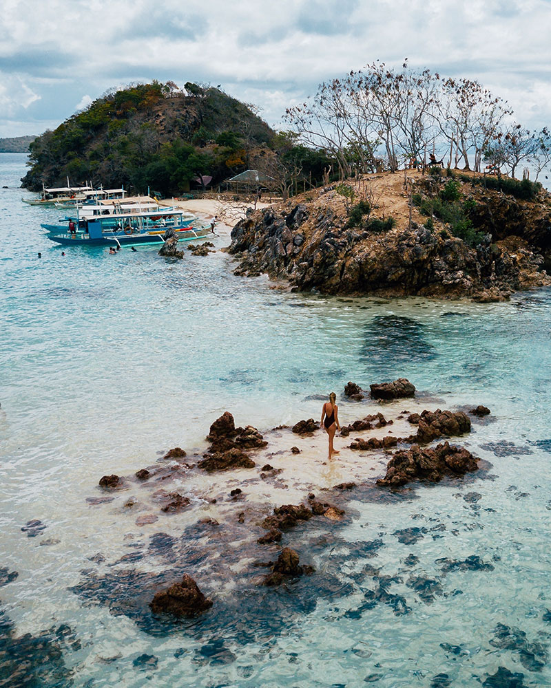 Drone shot of girl in the water at Bulog Dos Island, Coron, Philippines