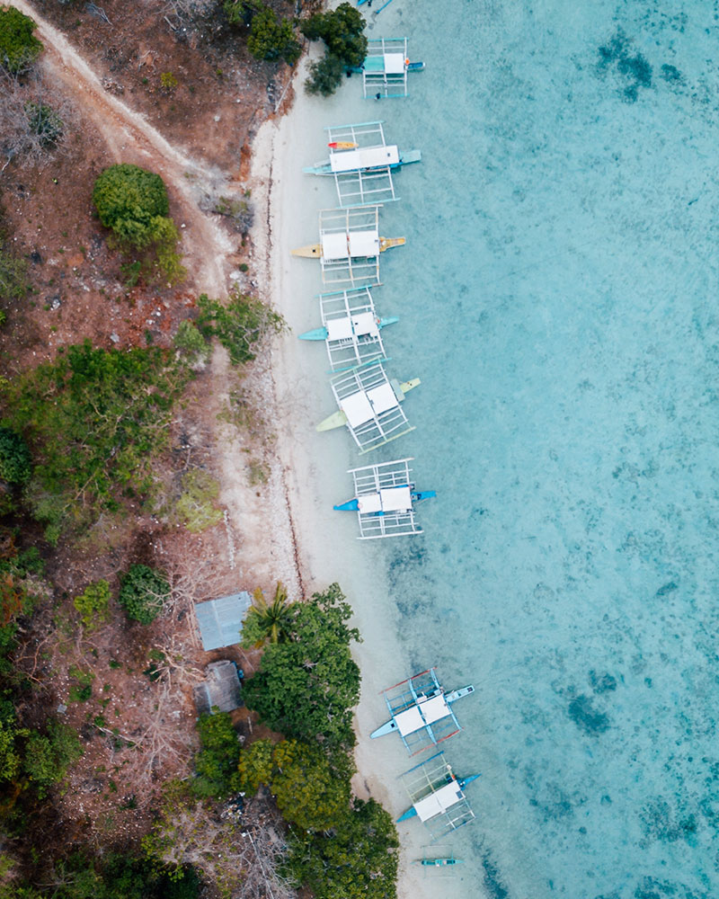 Drone shot with lots of boats at Macalpuya Island on Coron Island in the Philippines