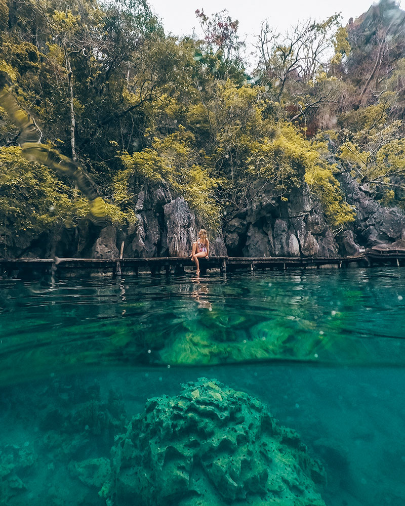 Boat trip in Coron, Philippines. View over Kayangan lake from under the water with girl sat on walkway