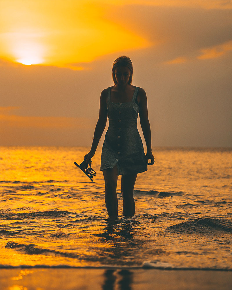 Girl standing in the water at Pantai Tegal Wangi with the sunset behind