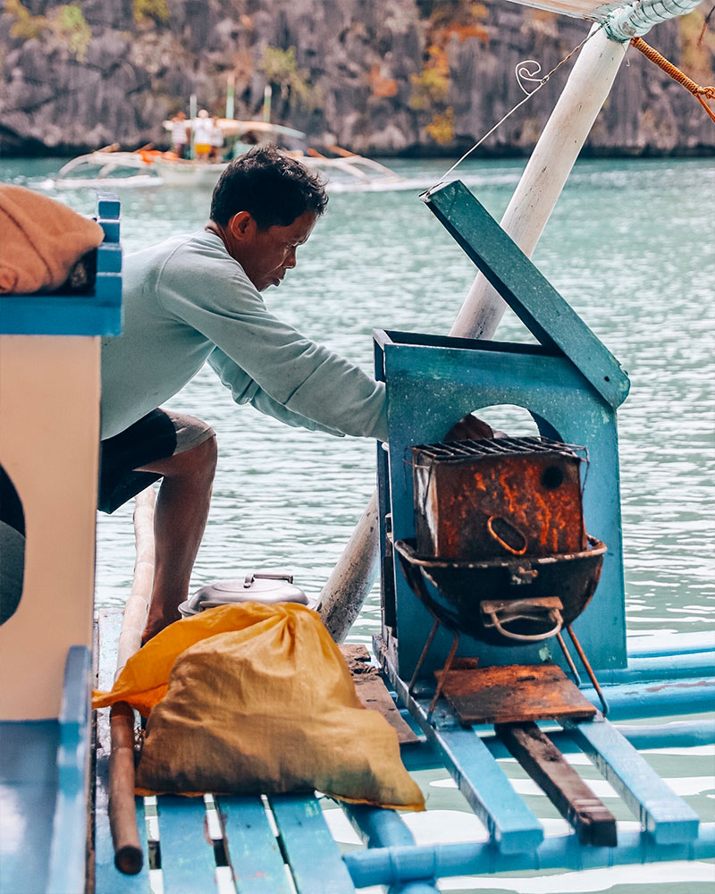 Man making a barbecue on the boat while island hopping in Coron Island in the Philippines