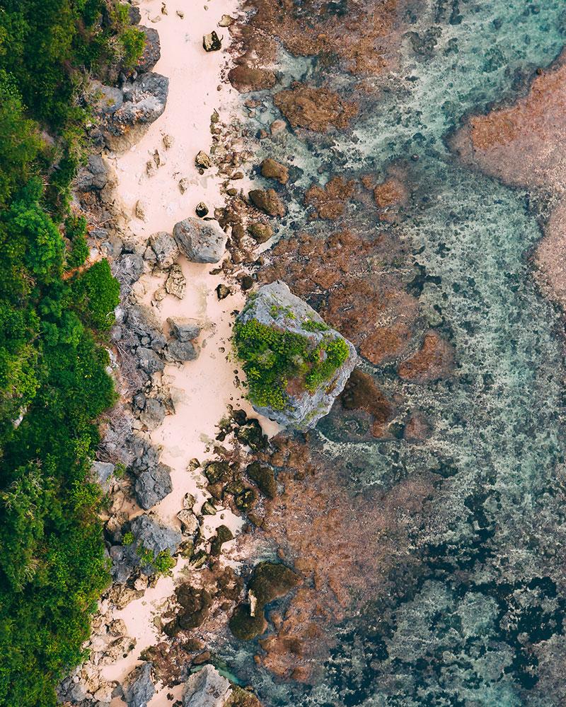 Drone photo of the beach at Uluwatu, Bali, Indonesia, sand sea and greenery