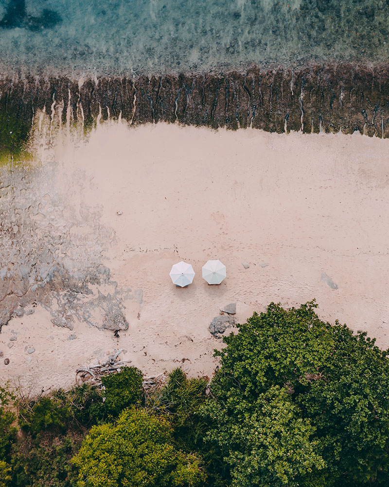Drone shot top down over Thomas Beach, sand and sea and a sun lounger, Uluwatu, Bali, Indonesia