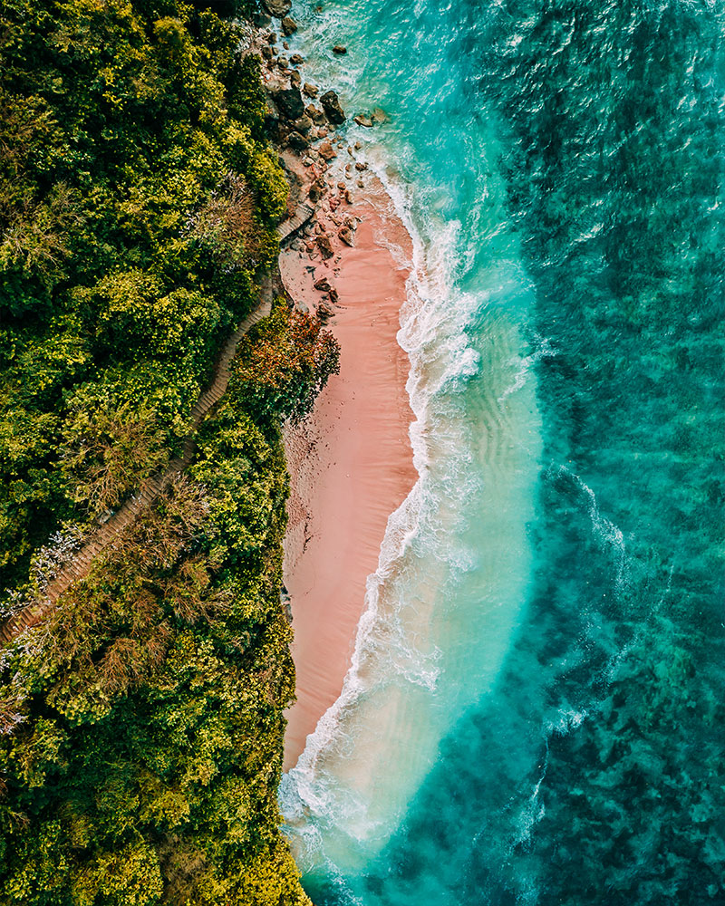 Drone shot of Green Bowl Beach, Bali - with sand and waves crashing onto the beach and greenery behind the beach