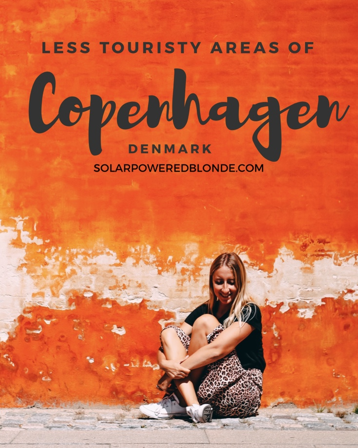 Pinterest text with me sat in front of an orange wall in Copenhagen