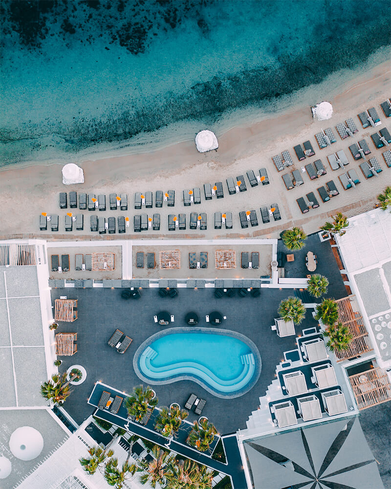 Drone shot of a beach in mykonos, greece, on the beach with sand and sea