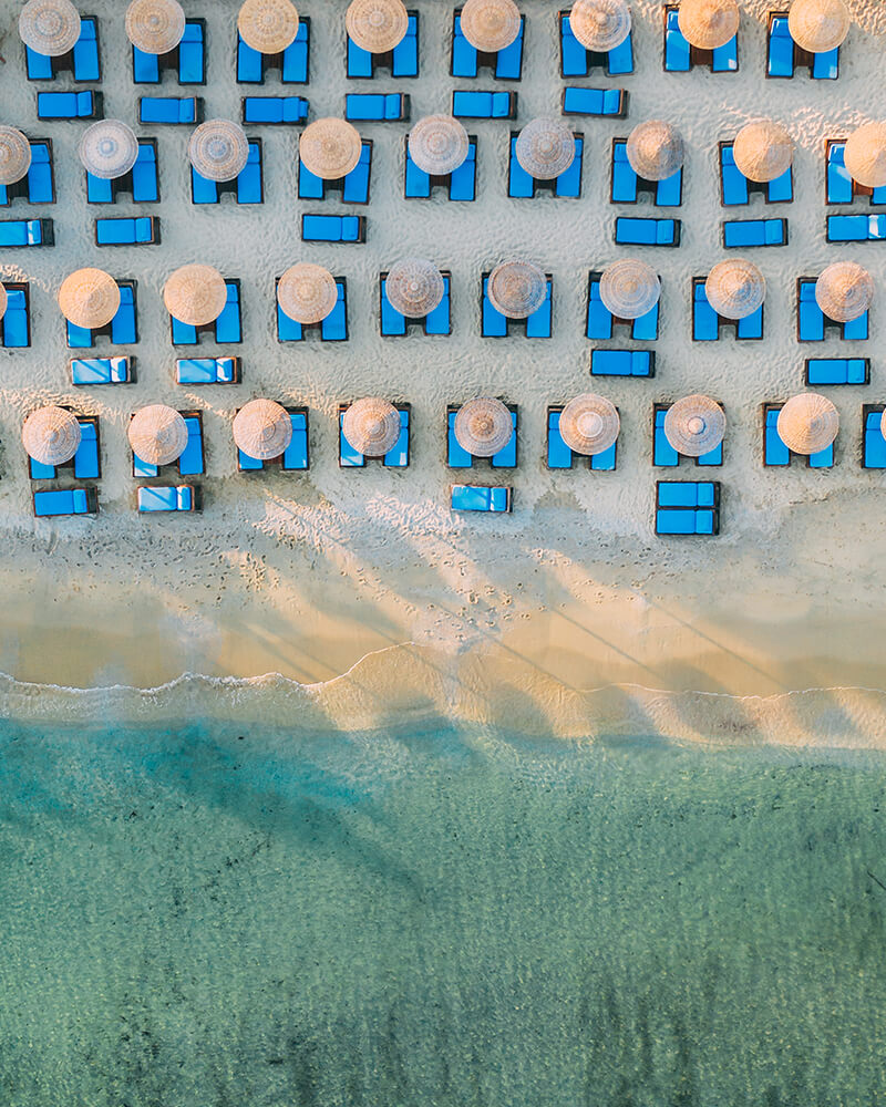 Paradise beach from above with sun loungers and sand and sea with waves, mykonos, greek islands