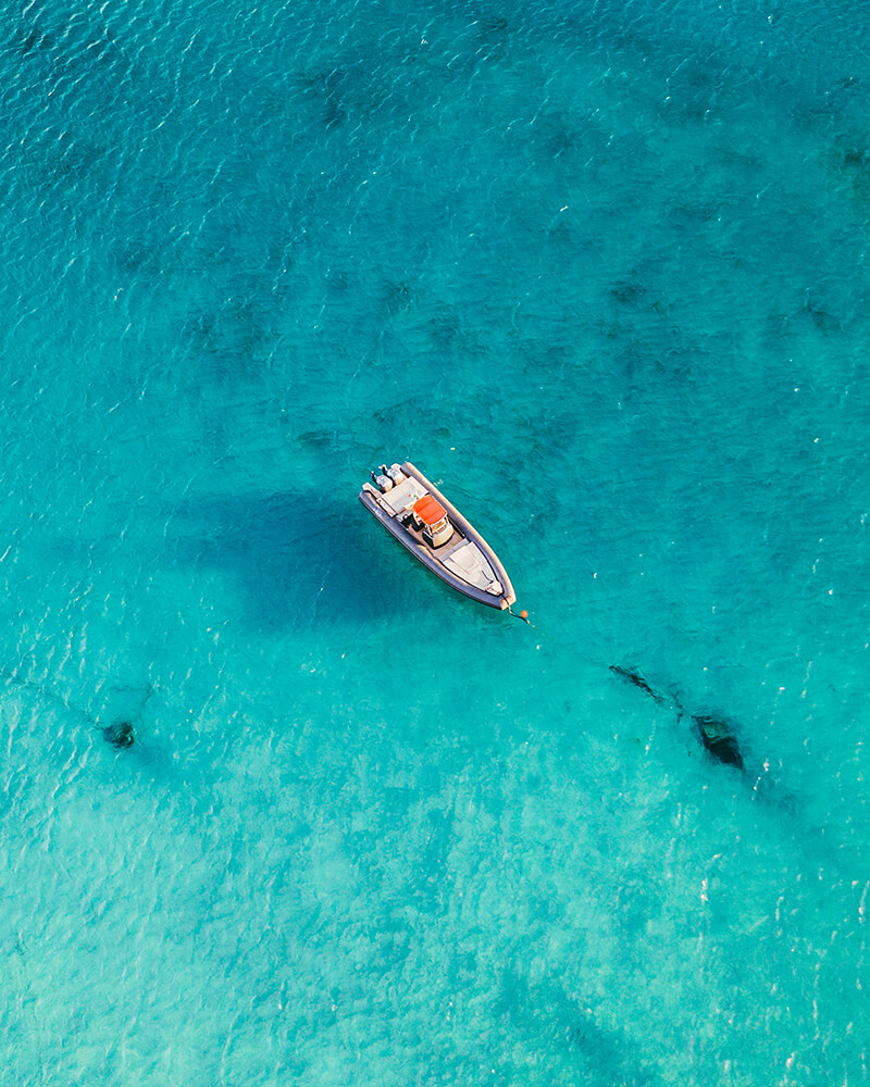 Drone shot of a boat in the middle of the blue sea in Mykonos