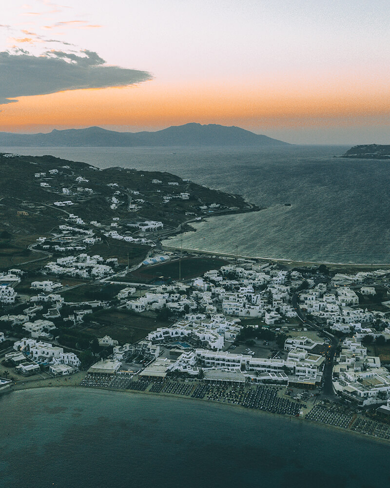 Drone shot of Ornos beach at sunset in Mykonos, Greece