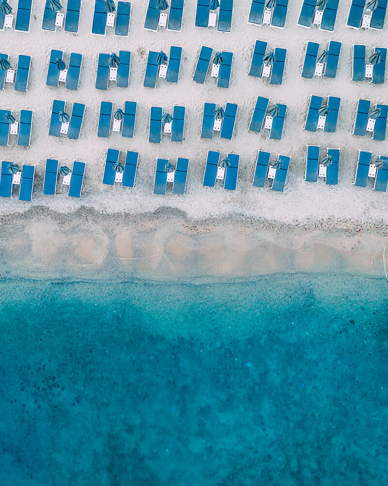 Drone shot of Elia beach in Mykonos, with sun loungers and blue sea