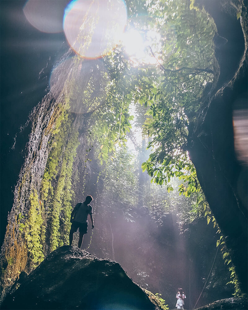 Tukad Cepung waterfall in Ubud, Bali. Man standing on a rock in the waterfall with light rays