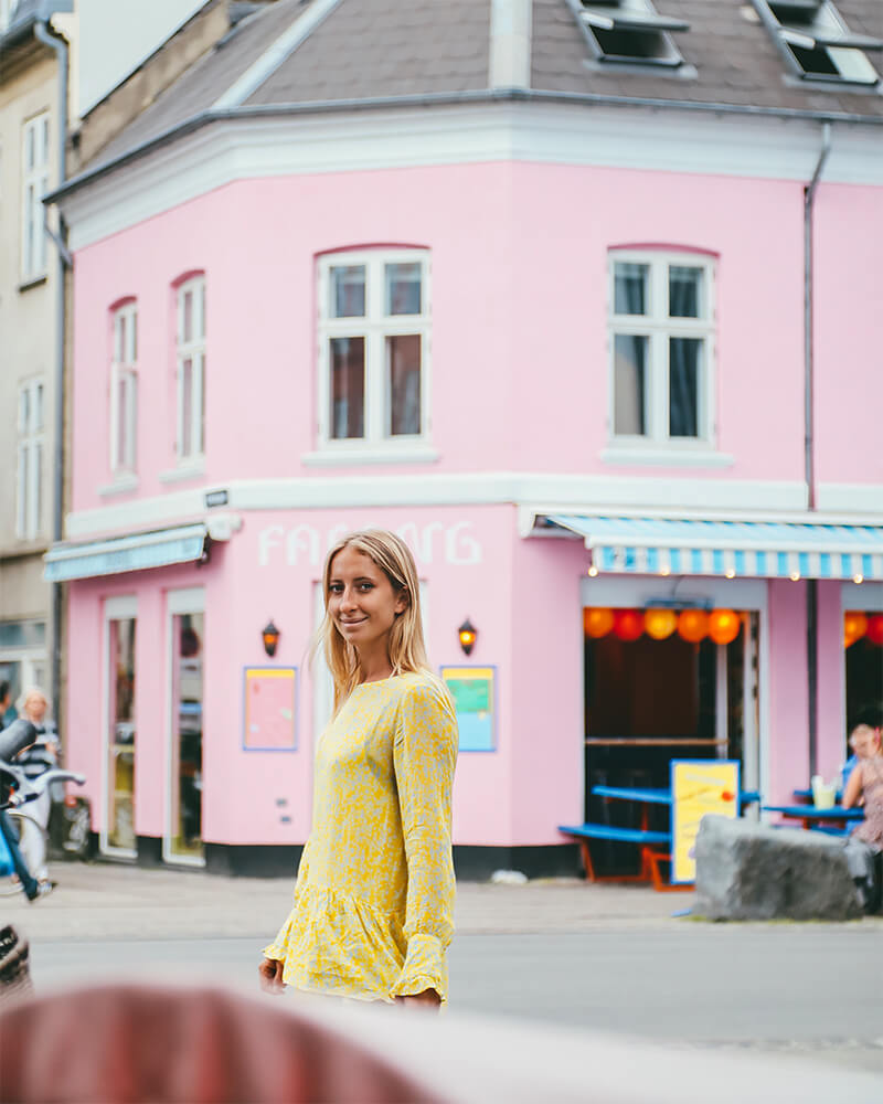 Me standing in front of a pink building in Vesterbro area in a yellow dress