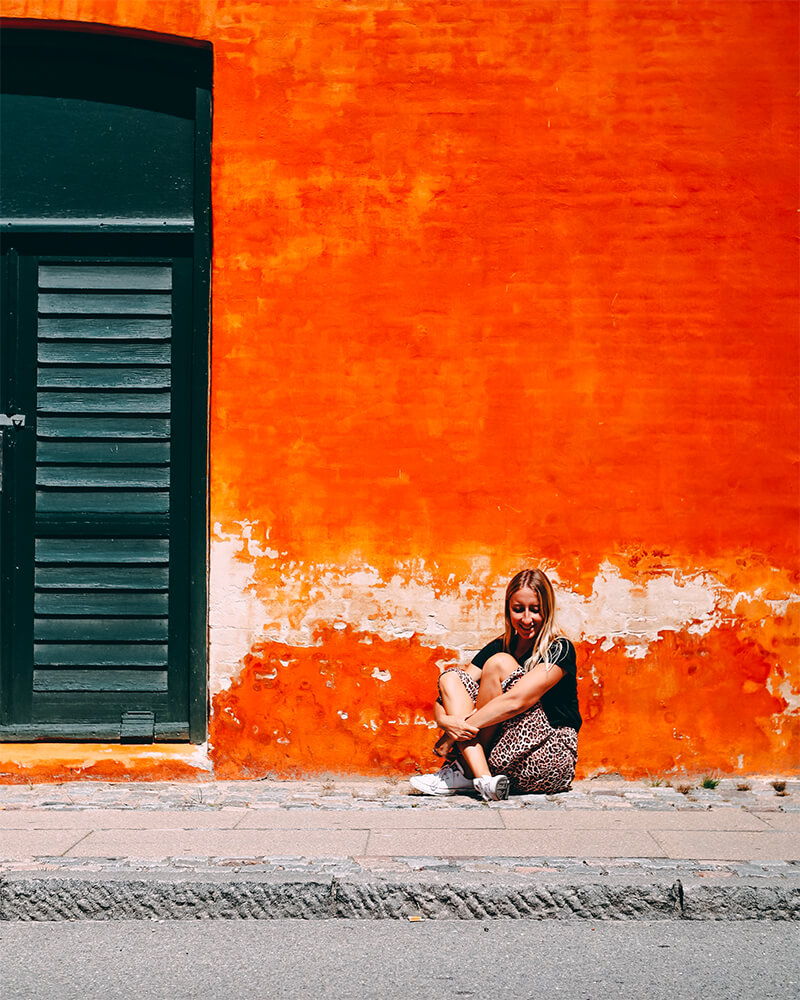 Me sat in front of an orange wall in Copenhagen