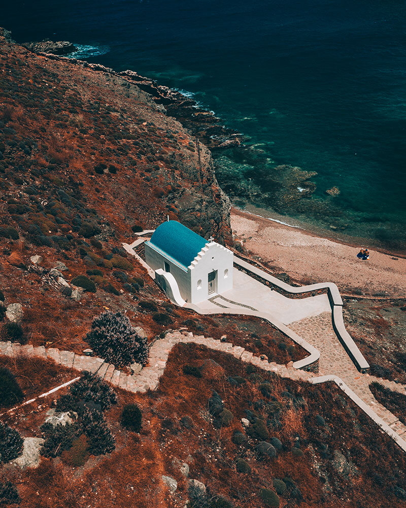 Fokos Beach in Mykonos, a secluded beach with a little church, drone shot