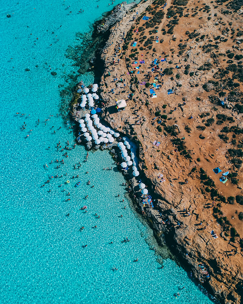 Drone shot of the blue lagoon at Comino in Malta with umbrellas on the beach on a day trip to comino