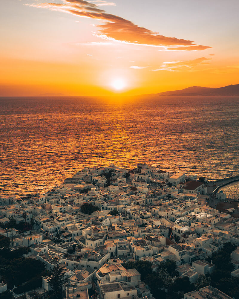 Sunset shot of Mykonos Town with white houses and orange sun in the distance
