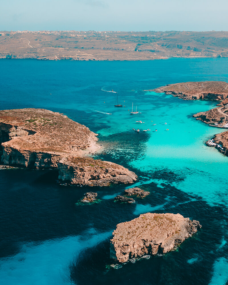 Drone shot of the Comino blue lagoon in malta, with rocks either side, during a day trip to comino