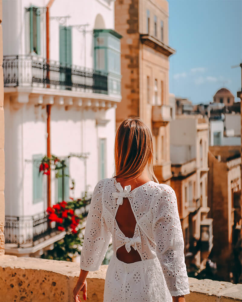 Me standing in a white dress in front of some buildings in valletta, Malta