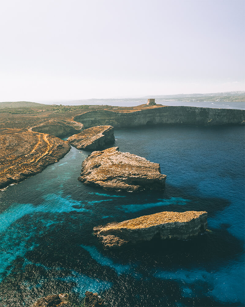 Drone shot over the blue lagoonat Comino, Malta with rocks and sea