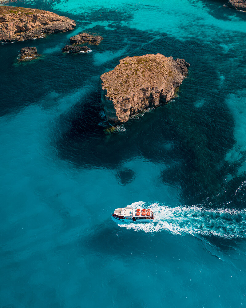Drone shot of the blue lagoon on a day trip to Comino, Malta, with a boat crossing the water