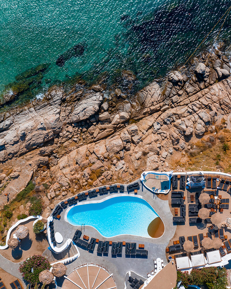 Jackie O Beach club and bar and restaurant taken from the drone, with pool and cliffs and sea