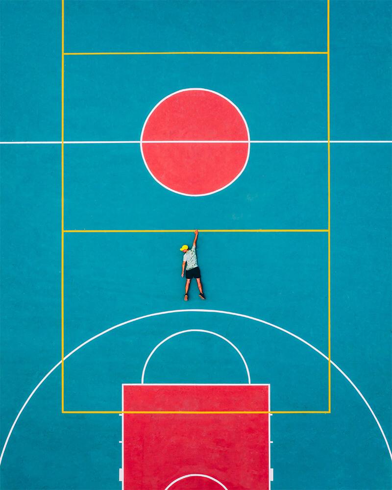 Boyan hanging off a basket ball court drone shot top down - creative drone photo ideas