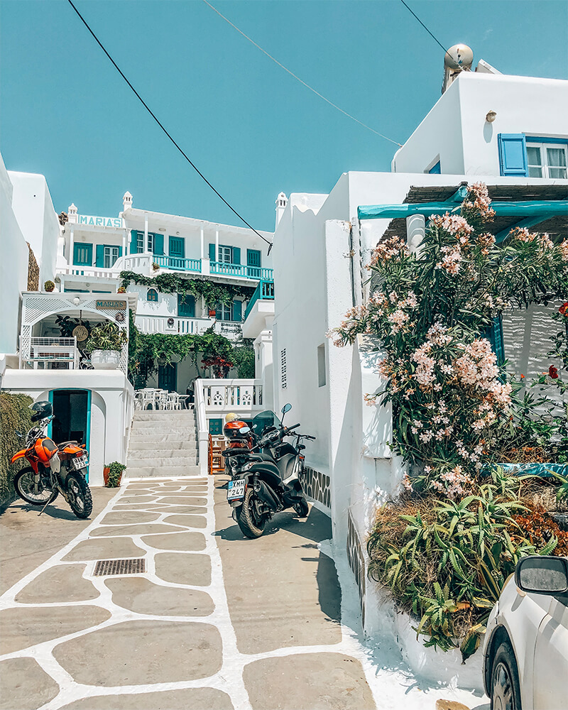 A little street in Mykonos with two bikes parked and flowers either side