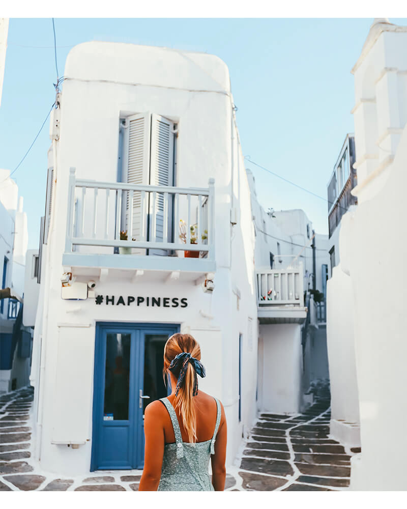 Instagrammble hashtag Happiness spot in Mykonos Town, and me standing in front - one of the best photography spots in Mykonos