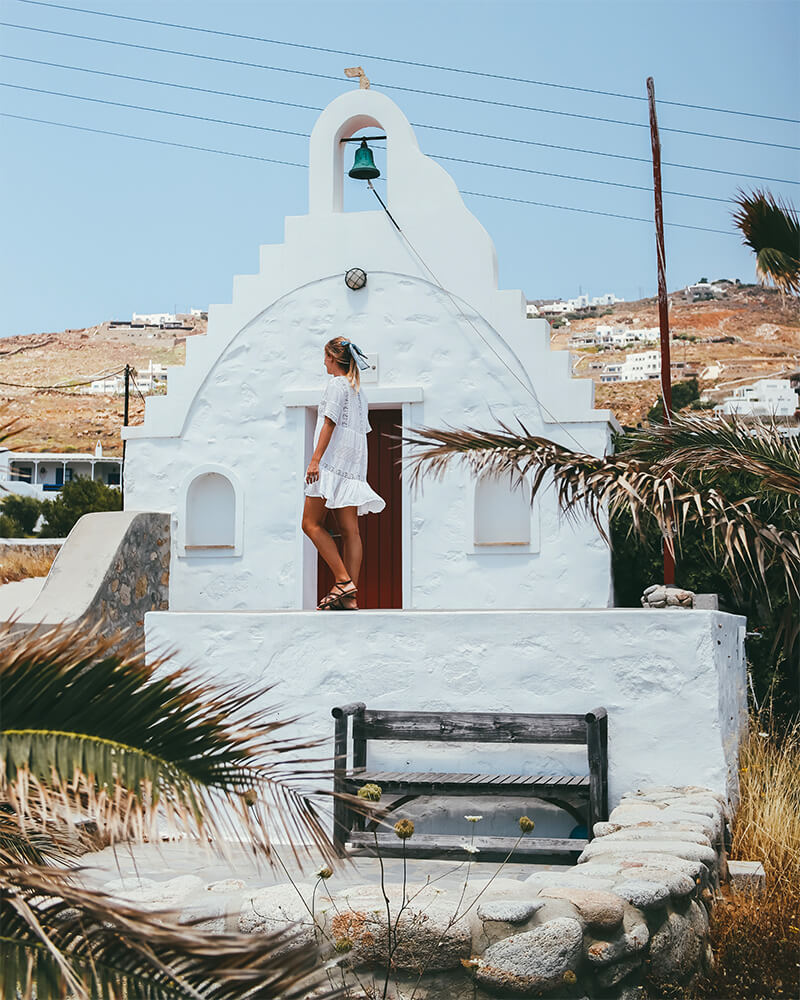 Me in front of a traditional church in Mykonos in a white dress