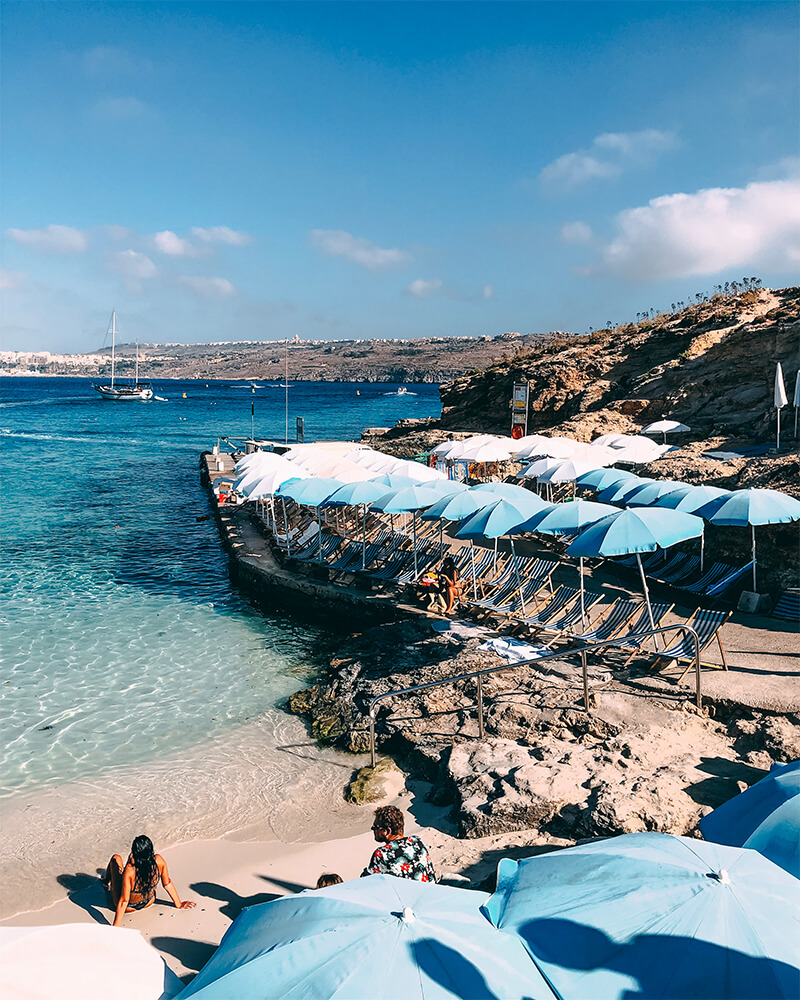 Beach at the blue lagoon in Malta with umbrellas and one woman sitting on the beach during a day trip to Comino