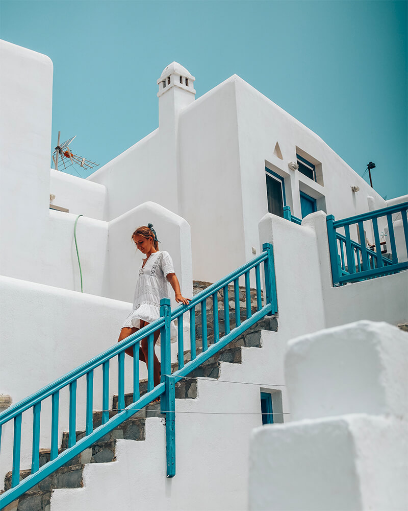 Me in the town of Ano Mera in Mykonos walking down a white set of stairs with blue railings