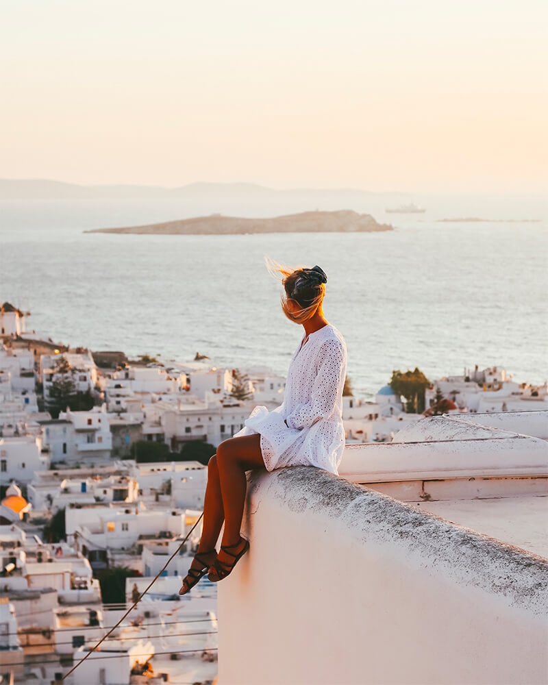 Me sat on a rooftop in Mykonos overlooking the town and all the houses at sunset