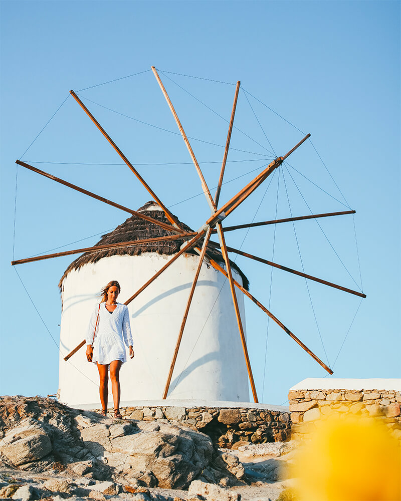 Famous Mykonos windmills with me walking in front of this best photography spot in Mykonos
