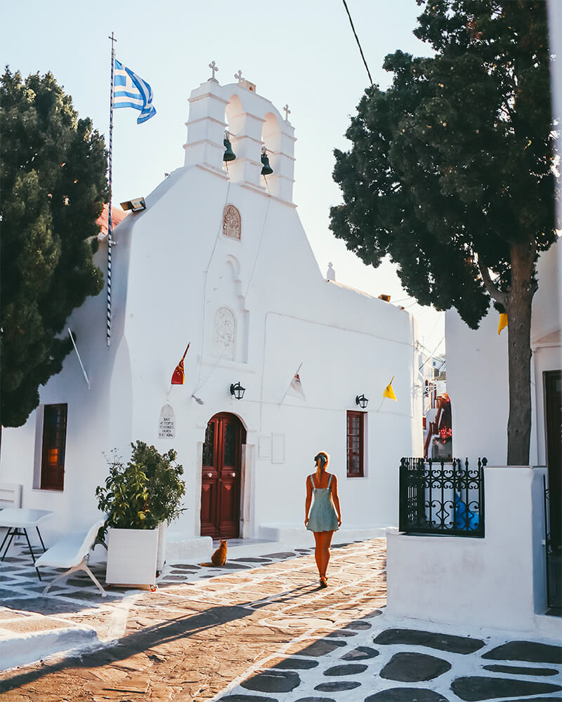A church in Mykonos Town, me walking in the sunrise in front of the best photography spots in Mykonos