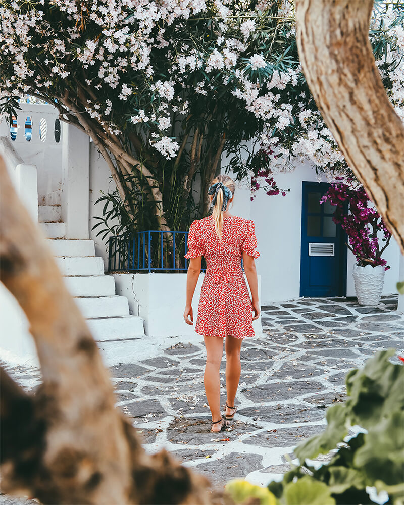 Me walking in the street in a red dress with flowers around in Mykonos Town - one of the best photography spots