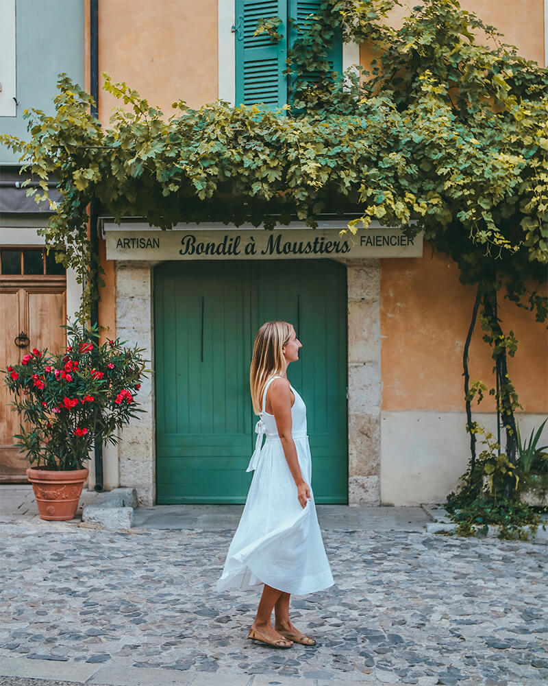 Solarpoweredblonde in front of a shop in Moustiers Sainte Marie wearing a white dress