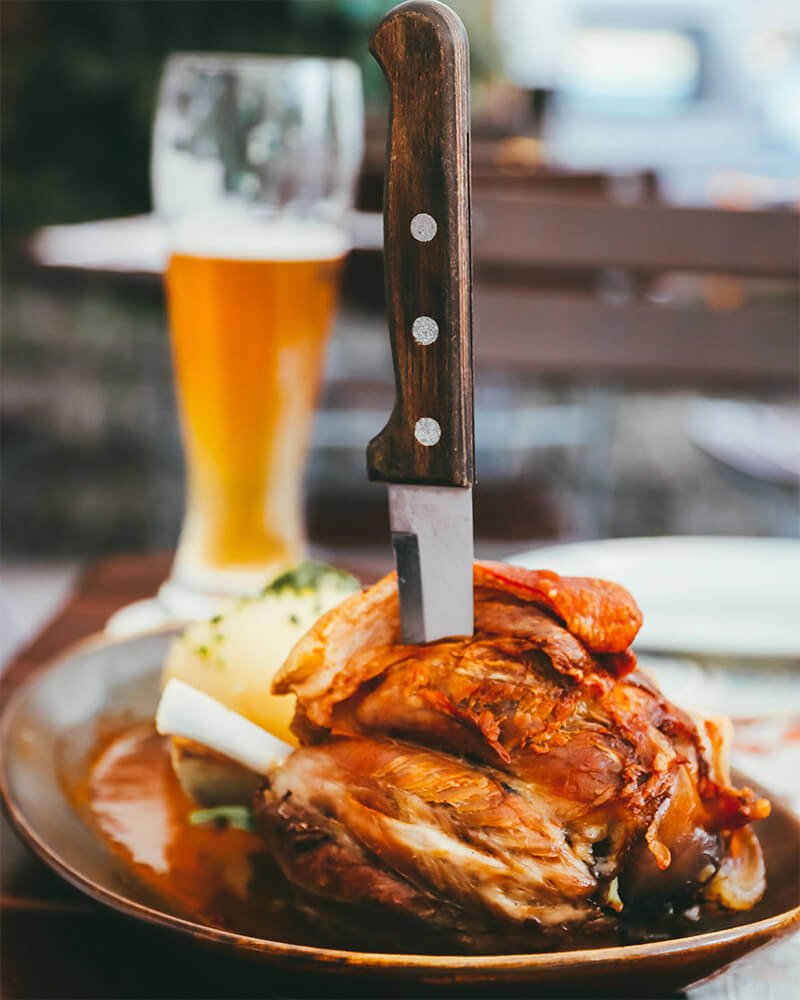 Photo of a pork knuckle with a knife in it