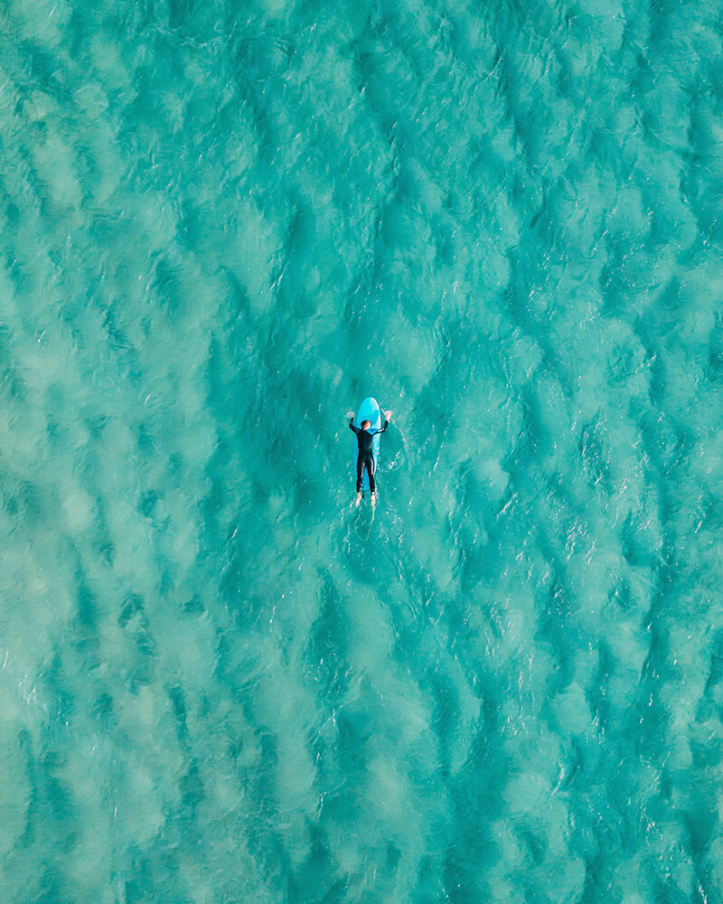 A man lying on his surfboard in the sea