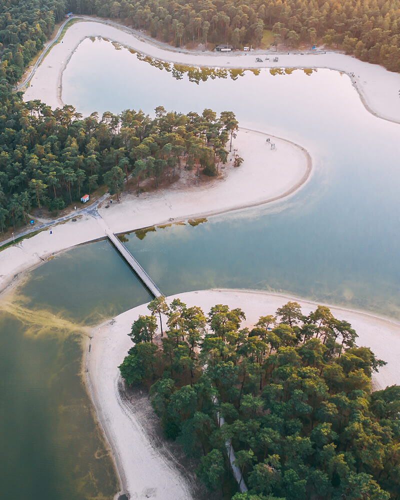 The inland beach in the Netherlands, drone shot of water and beach and trees