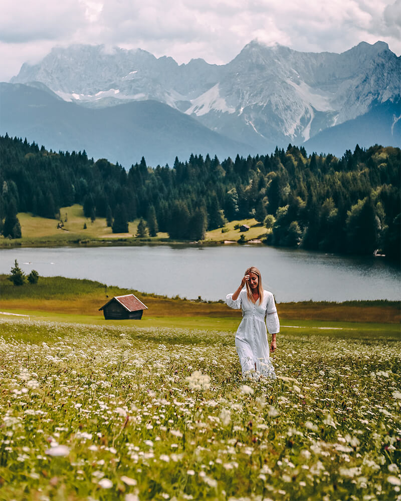 Me stood in a field with mountains behind and a lake, top things to do in bavaria in summer