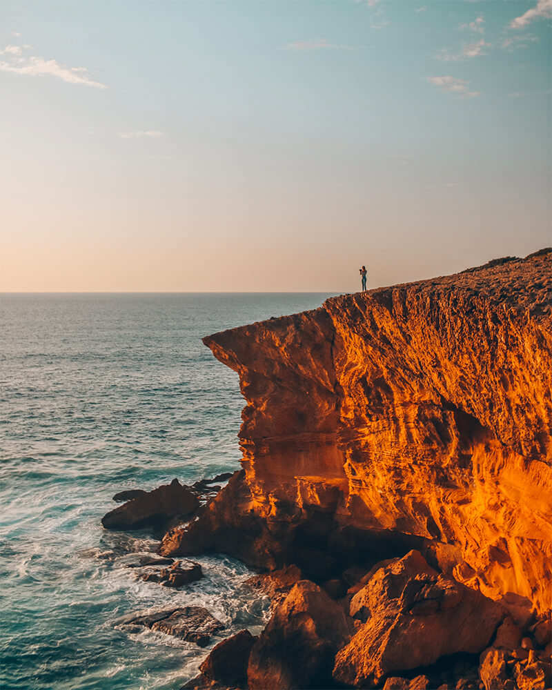 Me standing on a cliff at sunset - best 7 day Portugal itinerary