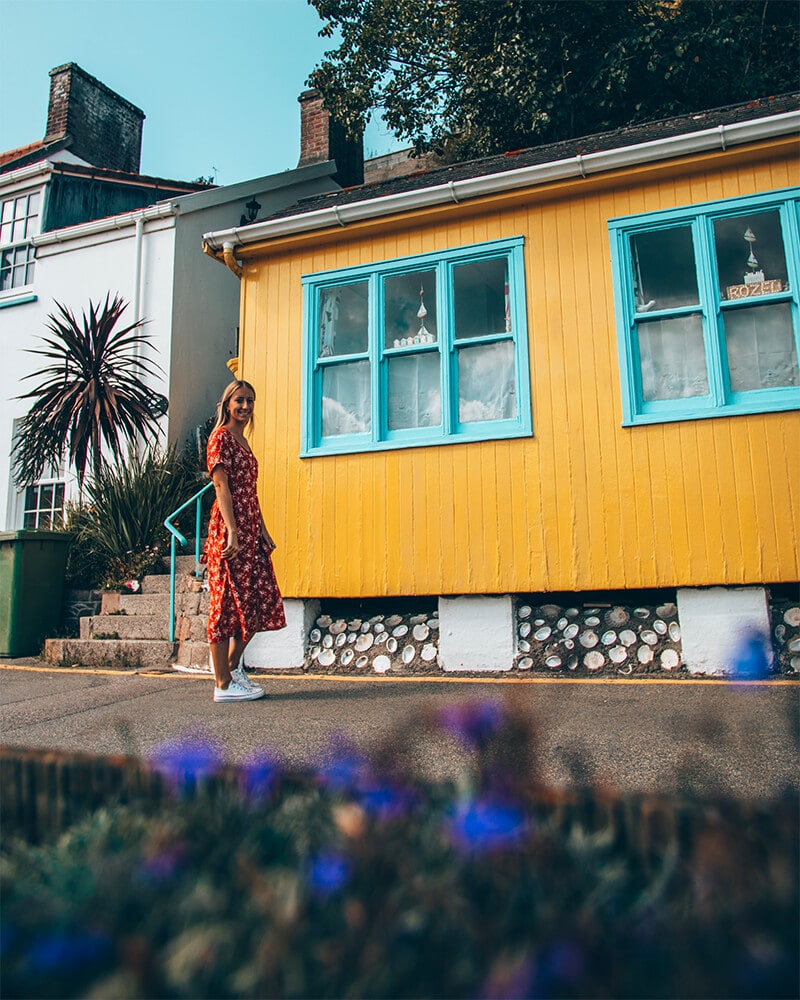 Me standing outside a colourful house near one of the best Jersey pubs and restaurants