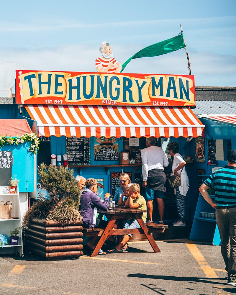People sat outside the Hungry Man food shack at the beach in Jersey