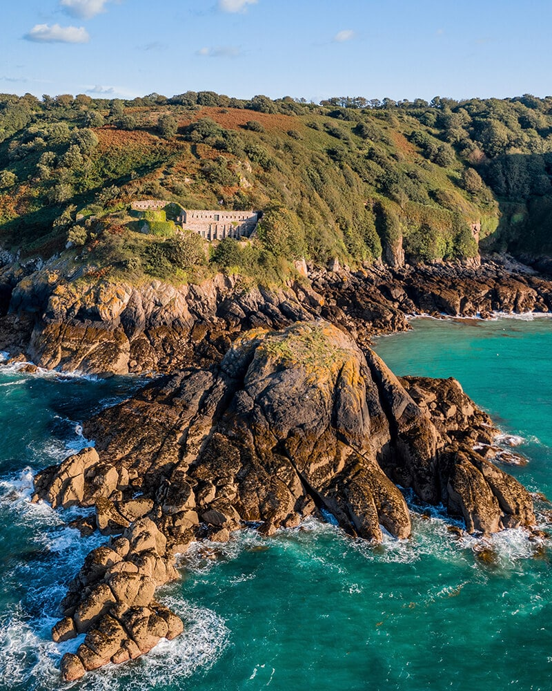Drone shot of the fort surrounded by greenery and rocks and sea, one of the best walks to the best beaches in Jersey