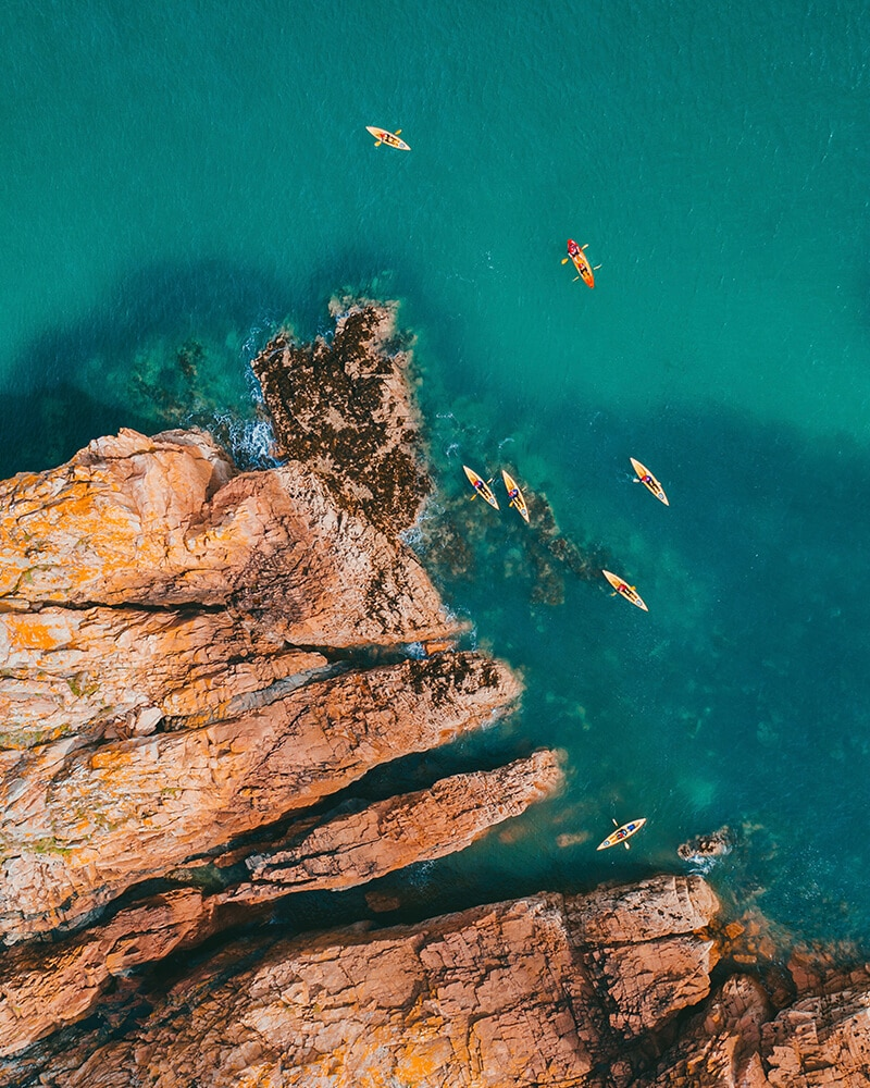 Drone shot of the sea and rocks with people kayaking