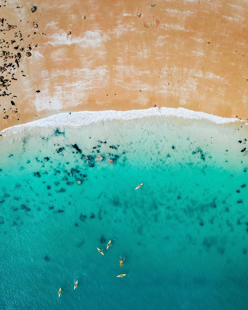 Drone shot of the beach in Jersey, UK with people kayaking